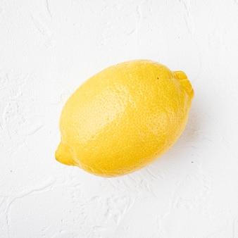Zestaw żółtych dojrzałych cytryn, na białym tle kamiennego stołu, z miejscem na tekst