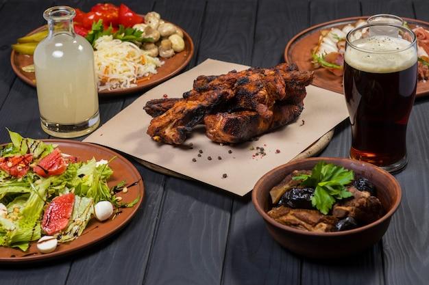 Zestaw żywności z grillowanymi żeberkami marynowanymi warzywami sałatka bekonowa i bimber na czarnym tle drewnianych