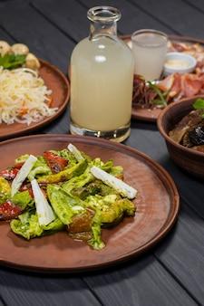 Zestaw żywności z grillowanymi żeberkami wieprzowymi sałatka z marynowanych warzyw i bimber na czarnym tle drewnianych