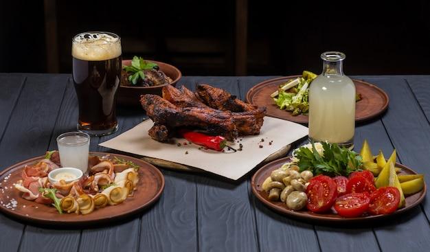 Zestaw żywności z grillowanymi żeberkami wieprzowymi szklankę ciemnego piwa na czarnym tle drewnianych