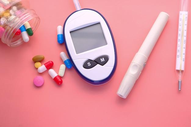 Zestawy do pomiaru cukru we krwi, tabletki i termometr na różowo