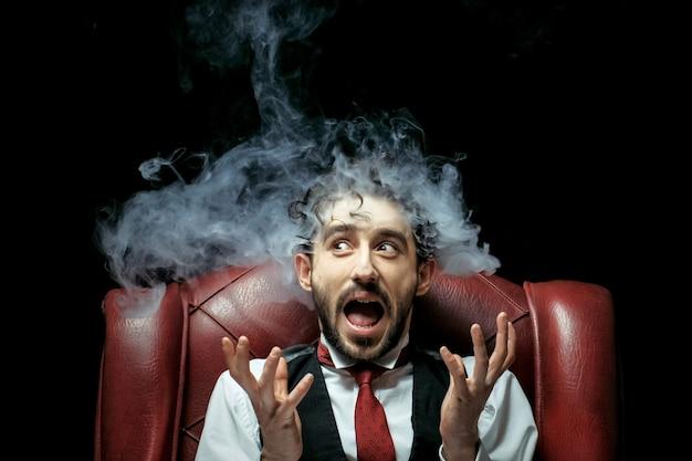 Zestresowana bizneswoman z dymem wydobywającym się z jego uszu