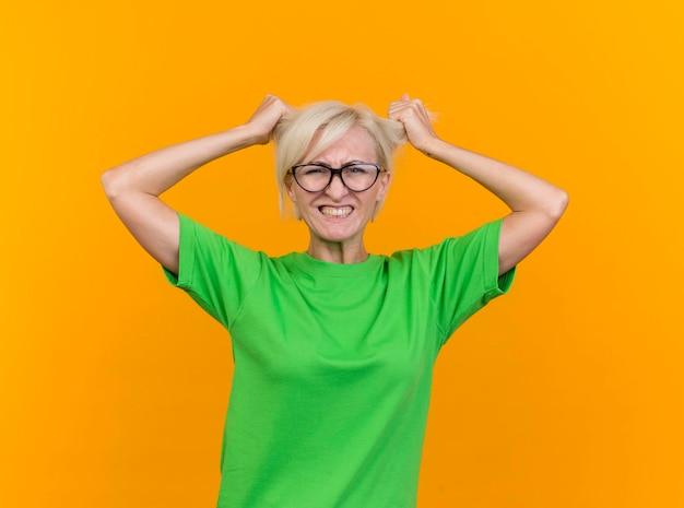Zestresowana blond słowiańska blondynka w średnim wieku w okularach patrząc na przód ciągnąc włosy na białym tle na żółtej ścianie