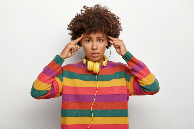 Zestresowana ciemnoskóra kobieta dotyka skroni, intensywnie myśli, ma bóle głowy, napotyka kłopotliwą sytuację, cierpi na bóle głowy, nosi luźny sweter w wielokolorowe paski, używa nowoczesnych słuchawek