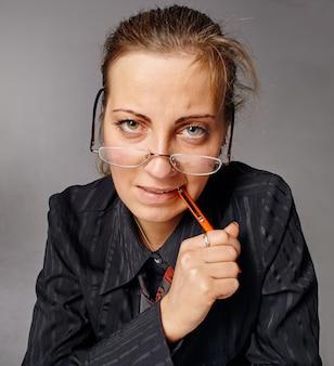 Zestresowana i wyczerpana kobieta spoglądająca przez okulary i gryząca pióro