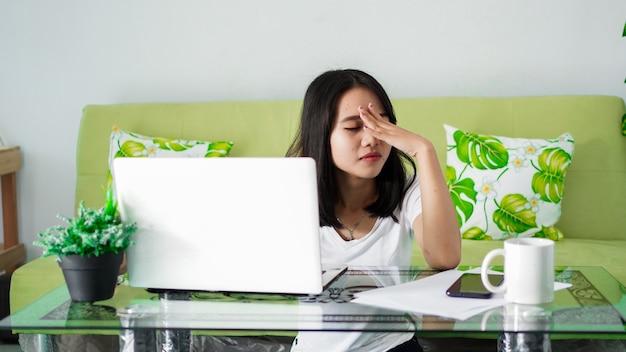 Zestresowana kobieta azji pracuje w domu z komputerem w domu