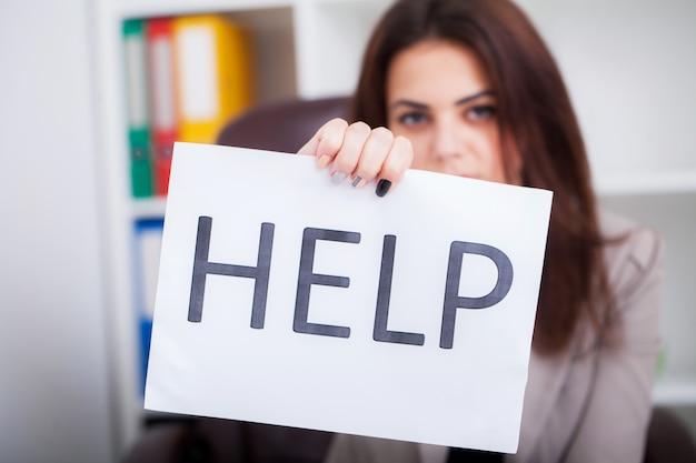 Zestresowana kobieta biznesu błagając o pomoc, trzymając karton z wiadomością pomocy