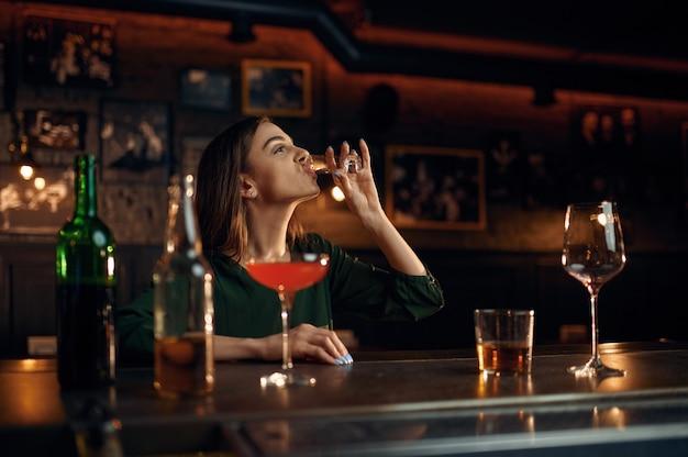 Zestresowana kobieta pije inny alkohol przy kasie w barze. jedna kobieta w pubie, ludzkie emocje, zajęcia rekreacyjne, życie nocne