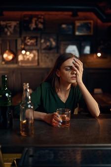 Zestresowana kobieta pije napój alkoholowy w barze