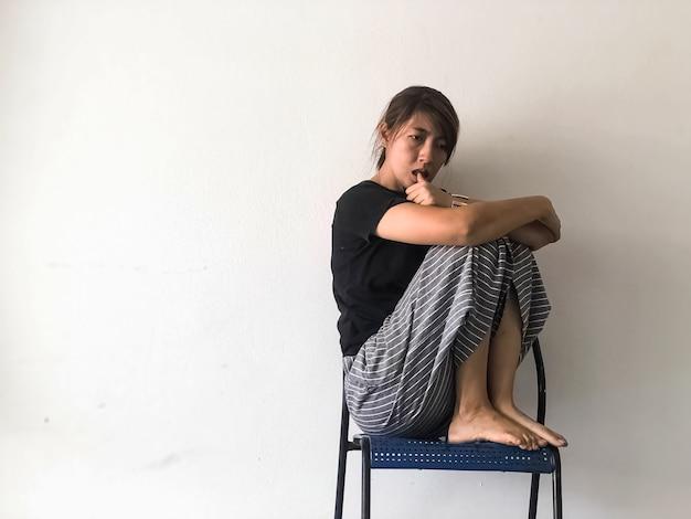 Zestresowana kobieta siedząca z wysokim kolanem na krześle gryzącym się w brzuch, ze zdenerwowanym i nieszczęśliwym uczuciem, zespół zaburzeń depresyjnych, poważne emocje