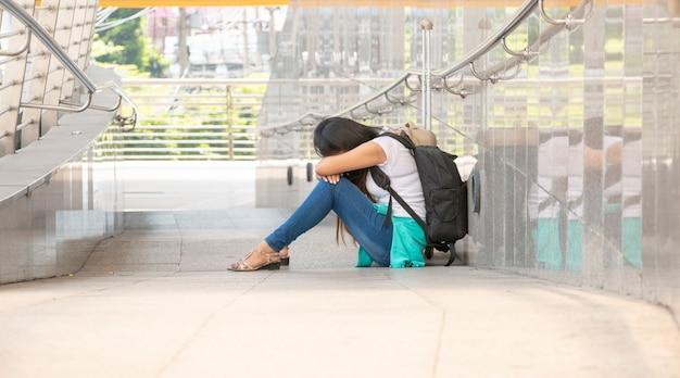 Zestresowana kobieta ucieka z domu. siedzi sama w terminalu ze smutkiem.