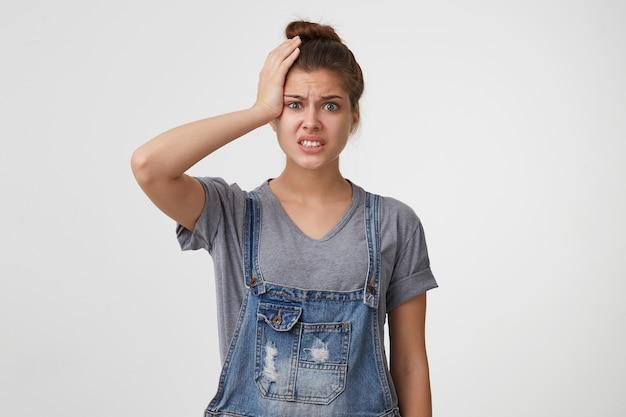 Zestresowana kobieta w dżinsowym kombinezonie chwyciła się za głowę w panice