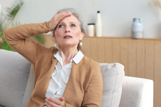 Zestresowana kobieta w średnim wieku siedzi na kanapie w salonie, zamyślona.