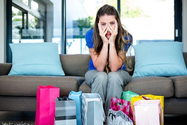 Zestresowana kobieta z głową w dłoniach otoczoną prezentami, siedząca na kanapie