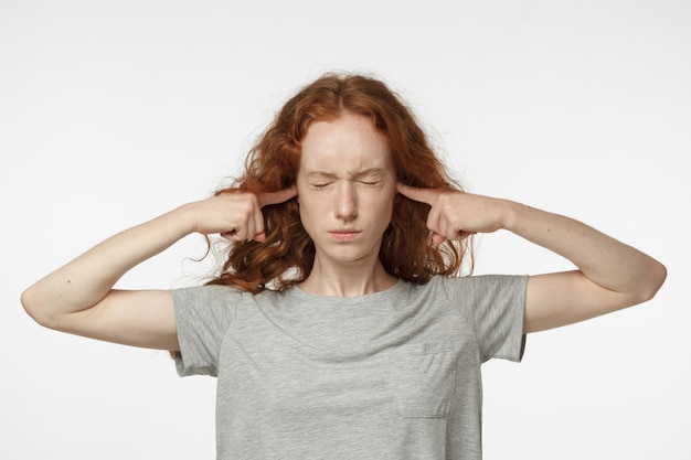 Zestresowana kobieta zatyka uszy, aby nie słyszeć odgłosów sąsiadów