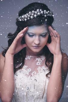 Zestresowana królowa śniegu wskazująca na padający śnieg