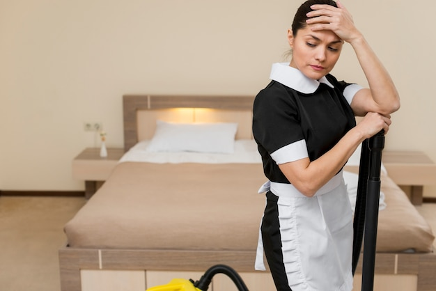 Zestresowana lub smutna pokojówka w pokoju hotelowym
