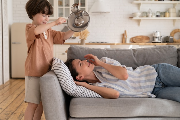 Zestresowana matka próbuje spać na kanapie, cierpi na ból głowy od niegrzecznego syna, który uderza w metalowe naczynia kuchenne