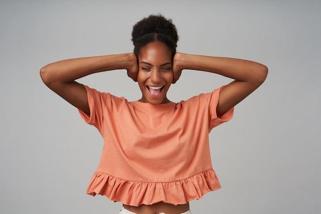 Zestresowana młoda atrakcyjna brunetka z kręconymi włosami, zamykająca uszy i krzycząca z zamkniętymi oczami, stojąca nad szarą ścianą w różowej bluzce