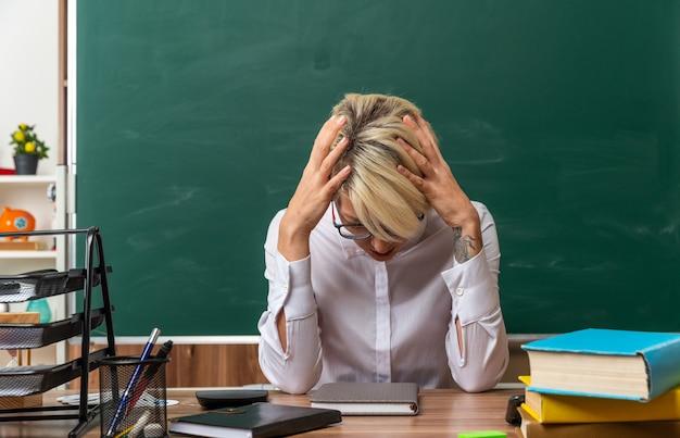 Zestresowana młoda blond nauczycielka w okularach siedzi przy biurku z szkolnymi narzędziami w klasie, trzymając ręce na głowie