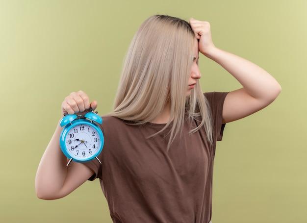 Zestresowana młoda blondynka trzyma budzik kładąc rękę na głowie na na białym tle zielonej ścianie