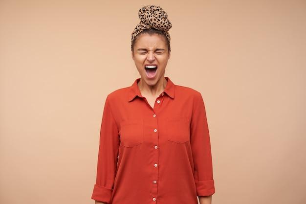Zestresowana młoda brązowowłosa brunetka kobieta z opaską marszczącą brwi i krzyczącą z zamkniętymi oczami, pozująca nad beżową ścianą z opuszczonymi rękami