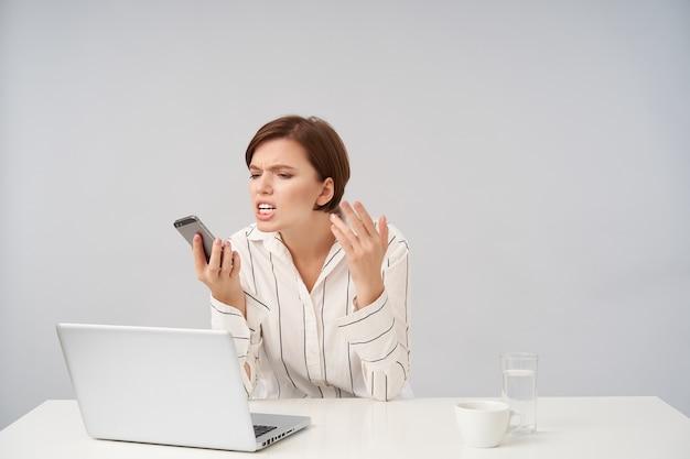 Zestresowana młoda brązowowłosa ładna kobieta biznesu, która ma ciężki dzień w pracy, trzymając telefon komórkowy w uniesionej ręce i patrząc na niego ze złością, na białym tle