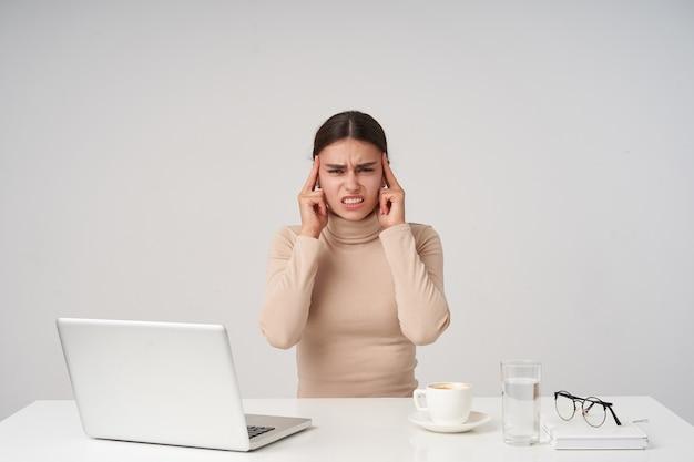 Zestresowana młoda ciemnowłosa kobieta z fryzurą w kucyk, trzymająca palce wskazujące na skroniach i marszcząca brwi, mająca silny ból głowy podczas siedzenia na białej ścianie