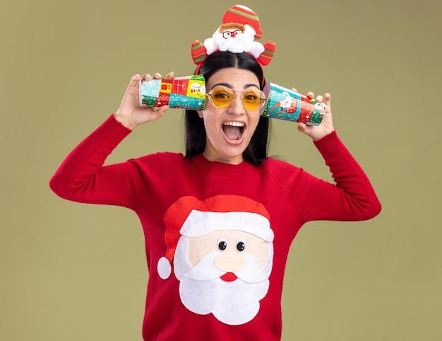 Zestresowana młoda kaukaska dziewczyna ubrana w opaskę świętego mikołaja i sweter w okularach trzymająca plastikowe kubki przy uszach słuchając rozmów krzyczących odizolowanych na oliwkowozielonej ścianie