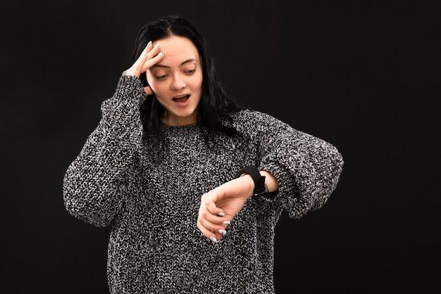 Zestresowana młoda kobieta czuje się zła, ponieważ się spóźnia. zdenerwowana kaukaski kobieta patrząc na czas i wskazując na zegarek