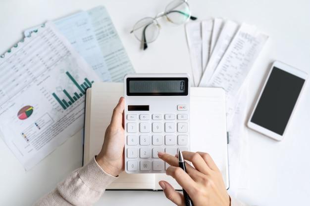 Zestresowana młoda kobieta obliczająca miesięczne wydatki na mieszkanie, podatki, saldo konta bankowego i płatności rachunków kartą kredytową, dochód nie wystarcza na wydatki