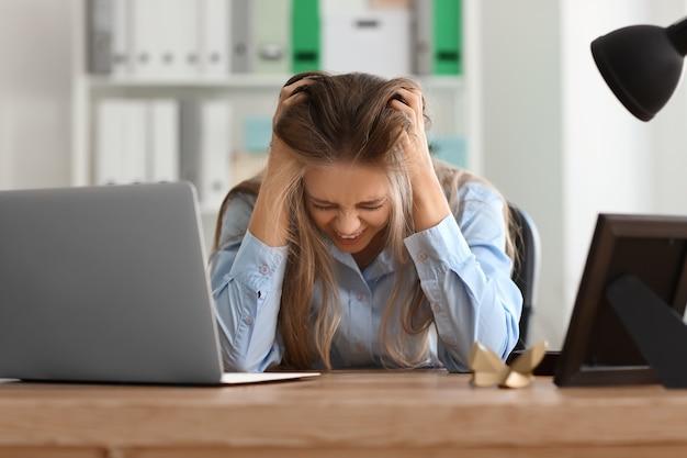 Zestresowana młoda kobieta w miejscu pracy