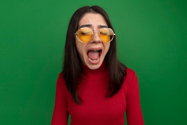 Zestresowana młoda ładna kaukaska dziewczyna w okularach przeciwsłonecznych krzycząca z zamkniętymi oczami na zielonej ścianie z kopią miejsca with