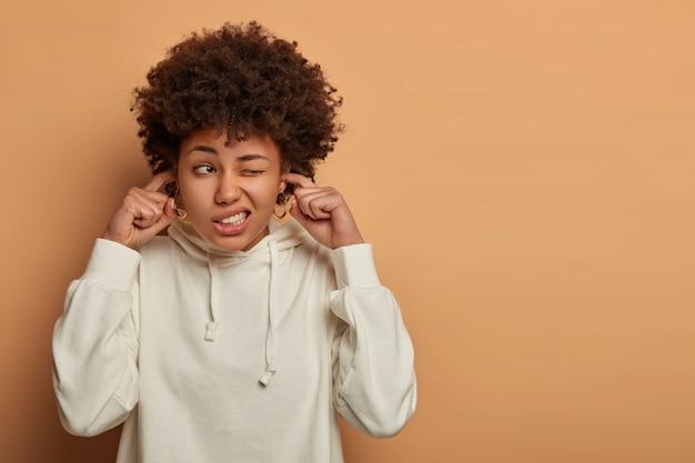 Zestresowana nerwowa kręcona kobieta zatyka uszy, zirytowana głośnym dźwiękiem