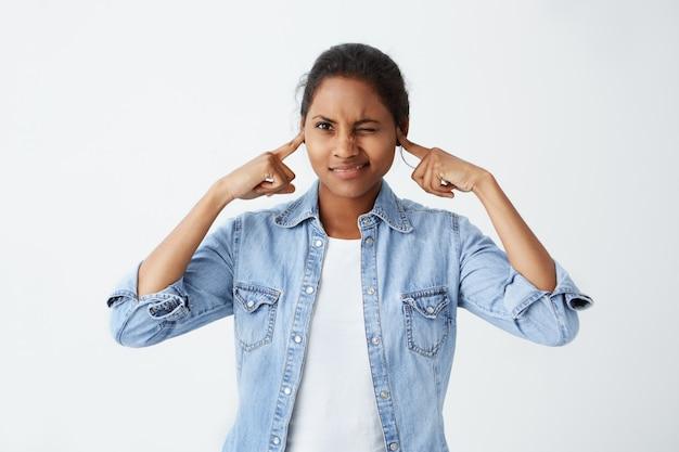 Zestresowana nerwowa młoda ciemnoskóra kobieta o czarnych włosach zamykających oczy i zatkających uszy palcami, zirytowana głośnym dźwiękiem lub muzyką dochodzącą z mieszkania sąsiada. przestań robić ten hałas