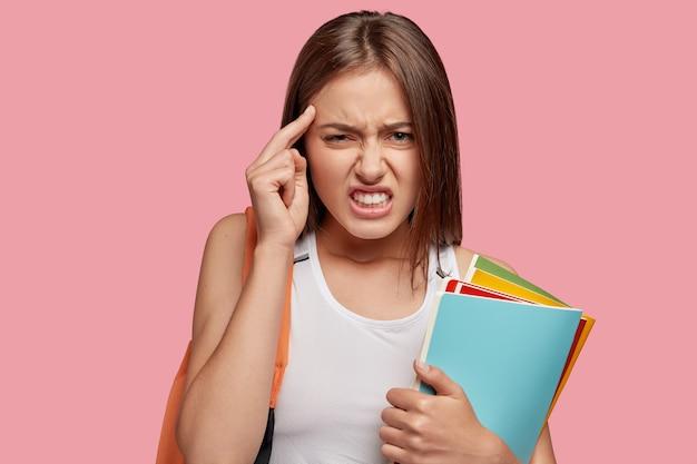 Zestresowana, niezadowolona młoda europejka trzyma palec wskazujący na skroni, ma ból głowy
