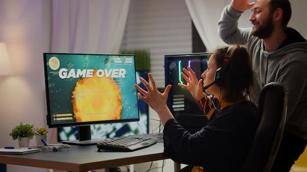 Zestresowana para graczy przegrywająca kosmiczną strzelankę grającą na potężnym komputerze rgb podczas przesyłania strumieniowego rywalizacji online. pro cyber kobieta z zestawem słuchawkowym występująca z domu podczas wirtualnego turnieju
