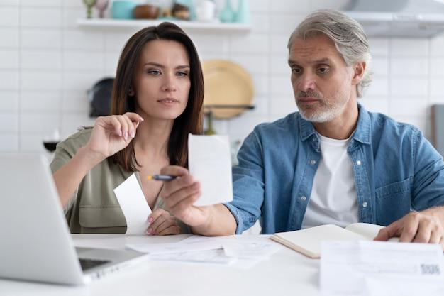 Zestresowana para rodzinna, rozczarowana wysokimi rachunkami za media, utratą pieniędzy. nieszczęśliwy zdenerwowany małżonek otrzymał powiadomienie o zaciągnięciu kredytu hipotecznego, sprawdzając dokumenty finansowe.