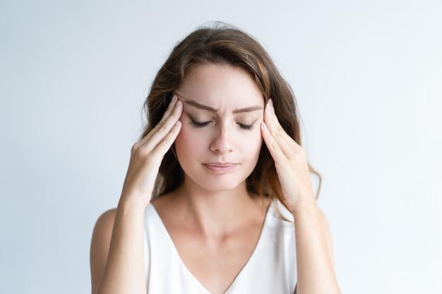 Zestresowana piękna kobieta dotyka świątynie i myśleć mocno