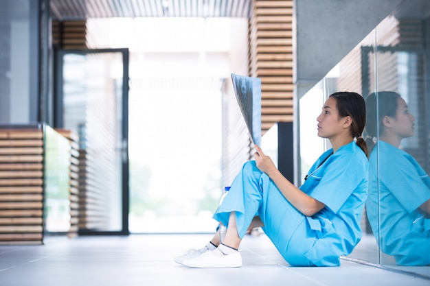 Zestresowana pielęgniarka bada raport rentgenowski