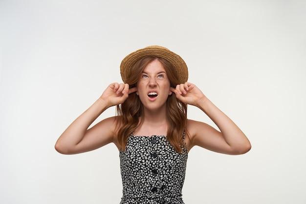 Zestresowana rudowłosa młoda kobieta w romantycznej sukience patrząca w górę z niezadowoloną twarzą, zamykająca uszy palcami wskazującymi, starająca się uniknąć irytujących dźwięków