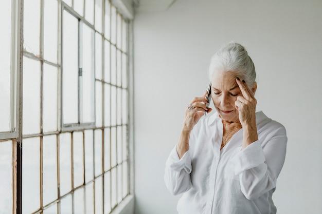 Zestresowana starsza kobieta rozmawia przez telefon przy oknie w białym pokoju