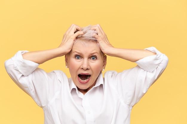 Zestresowana, wściekła emerytka krzyczy i wyrywa włosy, ma wściekły, zdesperowany wygląd, cierpi na ból głowy, wyraża negatywną reakcję. stres, rozpacz, zdenerwowanie i załamanie