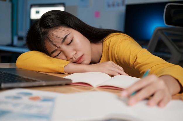 Zestresowana, wyczerpana kobieta siedzi przy biurku i pracuje w godzinach nadliczbowych, jest przeciążona pracą.
