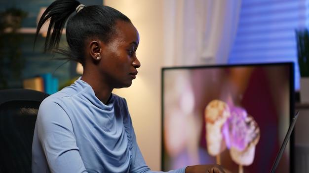 Zestresowana zajęta afrykanka z bólem głowy, pracująca w domu późno w nocy na laptopie. zmęczony, skoncentrowany pracownik korzystający z nowoczesnej technologii bezprzewodowej, wykonujący nadgodziny w celu czytania pracy, pisania, wyszukiwania