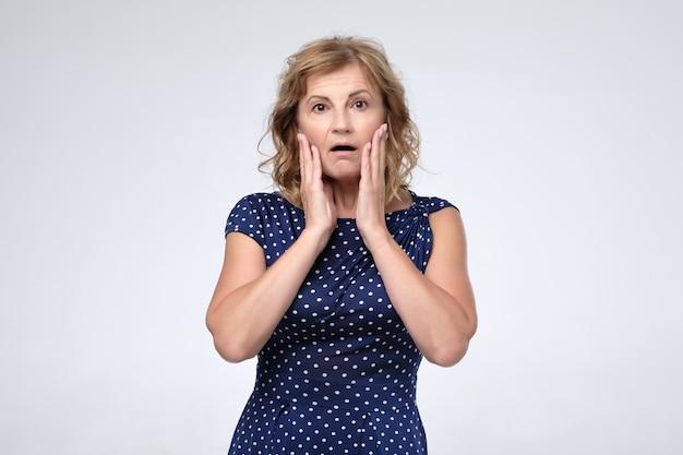 Zestresowana zdziwiona dojrzała kobieta martwiąca się o zmarszczki na twarzy