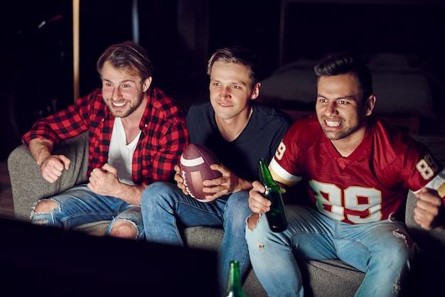 Zestresowani mężczyźni oglądają mecz w skupieniu