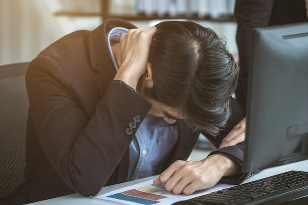 Zestresowany biznesmen pracował z laptopem i ból głowy po stratach biznesowych w tle pokoju biurowego.