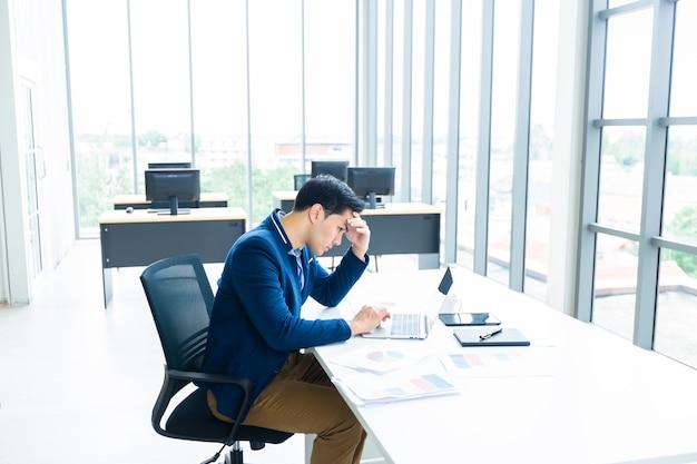 Zestresowany biznesmen pracował z laptopem i miał ból głowy po stratach biznesowych w pokoju biurowym.
