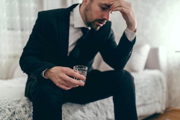 Zestresowany biznesmen siedzi na kanapie w garniturze, pije alkohol i trzyma rękę na głowie.